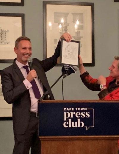Brent Meersman hands Pippa Green a cartoon by Tony Grogan